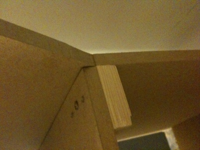 A wood block positioned so all screws go through MDF faces